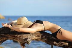 晒日光浴在海滩睡觉的健身妇女 免版税库存照片