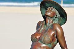 晒日光浴在海滩英属黄金海岸的被镀青铜的美丽的比基尼泳装女孩 免版税图库摄影