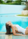 晒日光浴在游泳池边的愉快的少妇 免版税图库摄影