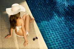 晒日光浴在游泳池附近的美丽的妇女 免版税库存图片