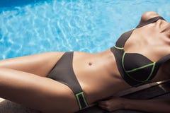 晒日光浴在游泳池附近的美好的妇女身体 免版税库存图片