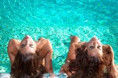 晒日光浴在游泳池 免版税库存图片