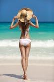 晒日光浴在热带海滩的古铜色Tan妇女 免版税库存图片