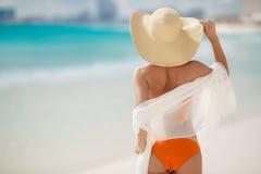 晒日光浴在热带海滩的古铜色Tan妇女 免版税库存照片