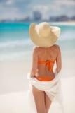 晒日光浴在热带海滩的古铜色Tan妇女 免版税图库摄影