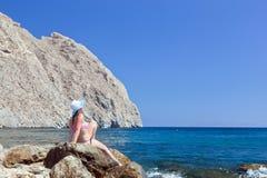 晒日光浴在热带海滩的岩石的年轻深色的美丽的妇女 免版税库存图片