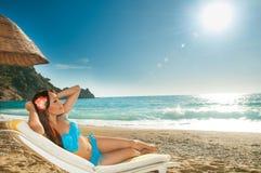 晒日光浴在的美丽的深色的女孩sunbed在海 免版税库存图片