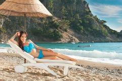 晒日光浴在的美丽的深色的女孩sunbed在海 库存图片