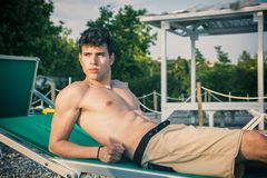 晒日光浴在躺椅的赤裸上身的年轻人  库存图片