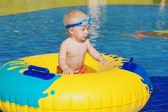 晒日光浴的孩子,与可膨胀的玩具的游泳在游泳池 免版税库存图片