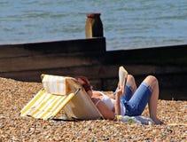 晒日光浴的阅读书 库存照片