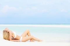 晒日光浴美好的海滩假日的妇女 免版税库存图片