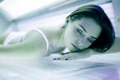 晒黑在日光浴室的美丽的妇女 免版税库存照片