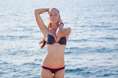 晒黑在海滩的游泳衣的女孩 免版税库存图片