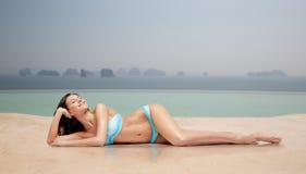 晒黑在游泳池的比基尼泳装的愉快的妇女 免版税库存图片