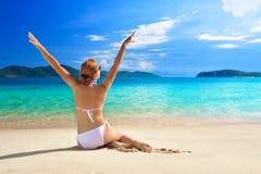 晒黑在白色沙滩的一种好心情的俏丽的妇女 免版税库存图片