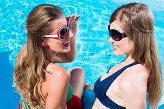 晒黑在水前面的游泳池的女朋友 免版税库存图片