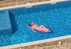 晒黑在水池的床垫的性感的妇女顶视图 免版税图库摄影