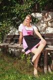 晒黑的少女装的女孩在长凳 免版税图库摄影