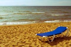 晒黑的Sunbed在样式人造偏光板的含沙海岸 免版税库存图片