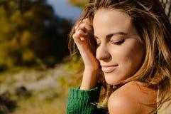 晒黑绿色的毛线衣的美丽的年轻女性  免版税库存图片