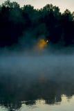 破晓在有雾和太阳的第一光芒的河 美好的金黄日出通过季节的有薄雾的森林概念 图库摄影