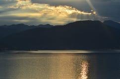 破晓在海,一座山在背景中 免版税库存照片