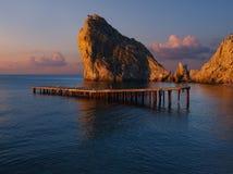 破晓在黑海在Simeiz地区:在水和一个木老码头的蓝色表面的中间一个巨大的岩石在lo 免版税图库摄影