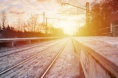 晚上与火车站的冬天风景 在太阳光下的积雪的铁路平台在日落 peo的地方 免版税图库摄影