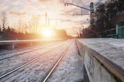 晚上与火车站的冬天风景 在太阳光下的积雪的铁路平台在日落 peo的地方 免版税库存图片