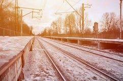 晚上与火车站的冬天风景 在太阳光下的积雪的铁路平台在日落 peo的地方 免版税库存照片
