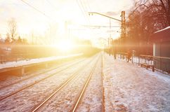 晚上与火车站的冬天风景 在太阳光下的积雪的铁路平台在日落 peo的地方 库存图片