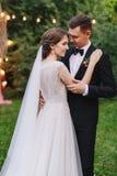 晚上与灯笼和灯的婚礼在树 拥抱在电灯泡光背景的新娘和新郎  库存照片