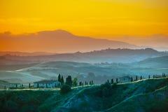 晚上在托斯卡纳 在金黄心情的多小山托斯坎风景在与柏和农厂房子剪影的日落时间  免版税库存照片