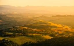 晚上在托斯卡纳 在金黄心情的多小山托斯坎风景在与柏和农厂房子剪影的日落时间  库存照片