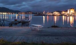 晚上在Lofoten海岛,挪威上的渔村点燃有对山的看法 免版税库存图片