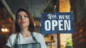 晚上垂悬的闭合的标志的美丽的女服务员结束咖啡馆在门 股票视频