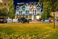 晚上城市的看法有高旅馆绿色草坪的一个美丽的大厦的和停放在边路乘汽车 免版税库存照片