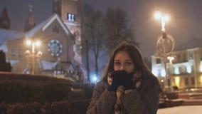 晚上城市背景的一个女孩给冷的手加热 根据城市光降雪 股票录像