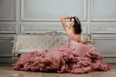 晚上多云礼服的豪华性感的女孩坐在演播室内部的一个沙发 库存图片