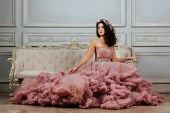 晚上多云礼服的豪华性感的女孩坐在演播室内部的一个沙发 免版税库存照片