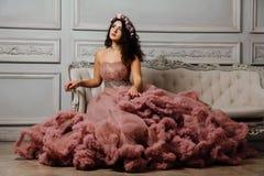 晚上多云礼服的豪华性感的女孩坐在演播室内部的一个沙发 免版税图库摄影