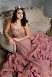 晚上多云礼服的豪华性感的女孩坐在演播室内部的一个沙发 图库摄影