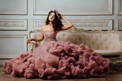 晚上多云礼服的豪华性感的女孩坐在演播室内部的一个沙发 免版税库存图片