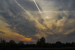 晚上天空、云彩和飞机转换轨迹 库存图片