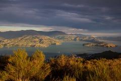 晚上太阳打开港口和周围的小山 免版税库存图片