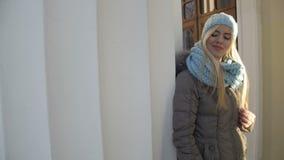晚上太阳温暖的光照亮在浅兰的冬天帽子和围巾打扮的微笑的夫人 股票录像