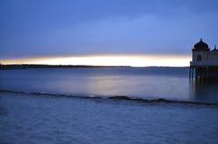 晚上太阳用光滑的水 免版税库存照片
