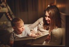 晚上家庭读书 母亲读孩子 在goin前的书 库存图片