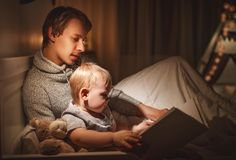 晚上家庭读书 父亲读孩子 在去前的书 库存照片